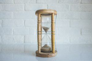 Wood hourglass and a white brick wall background